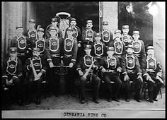 """The Germania Fire Engine House, built in the 1850's, was located on Madison Street. The building housed a hose cart, keel and other early fire fighting equipment. The Germania """"Fire Laddies"""" often participated in parades and other celebrations in which they wore their uniforms (pictured)."""