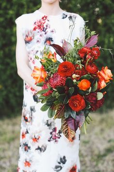 Red, orange, and leafy green bridal bouquet | Lara Hotz Photography