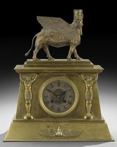 """Assyrian and Egyptian Revival Bronze Clock by Achille Brocot (French, 1817-1878), third quarter 19th century, winged scarab, pharaoh caryatids, Assyrian winged bull with a bearded human head, the clock works marked """"AB"""" flanking a star, for Achille Brocot, h. 15-1/4"""", w. 12-3/4"""", d. 5-1/4""""."""