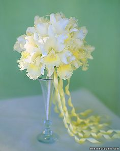 The soft ruffles of this ethereal ball of yellow-touched white Cattleya orchids trail off giddily into girlish curls of pale-yellow ribbon.