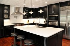 How amazing is this kitchen remodel? Love the white counter tops and black cabinets! Great work by All-In Construction!