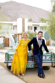 Perfectly dressed couple poses in front of vintage auto