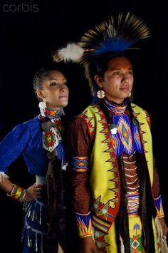 Traditional Teenage Couple:Native American teenage couple of boyfriend and girlfriend dressed in traditional pow wow dance regalia pose next to a black backdrop. Fort Hall, Idaho, USA. Marilyn Angel Wynn photography