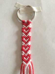Tarvikkeet – 100cm punaista lankaa x 2 -100cm valkoista lankaa x 2 -sakset -avaimenperärengas -teippiä 1. Aseta langat avaimenperään kuvan osoittamalla tavalla, niin että värit vuorottelevat …