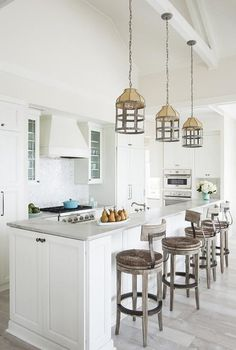 Beach style kitchen features three wood and metal cage lanterns illuminating a white wainscoted island with raised breakfast bar topped with honed marble lined with four wood and iron rush seat barstools, Lexington Twilight Bay Dalton Counter Stool.