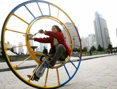 """A woman rides an unicycle at a park in Shanghai February 28, 2004. The unicycle was designed several years ago by Chinese inventor Li Yongli who called it """"the number one vehicle in the world""""."""