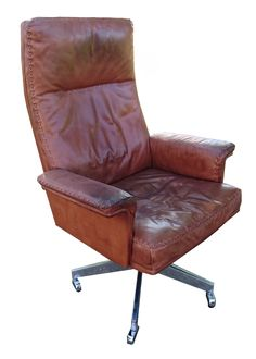 A DS35 High Back Executive Swivel Office/ Lounge Chair by De Sede of Switzerland. Dating to the 1960s, this chair is upholstered in tan leather with whipstitch detailing. The swivel armchair stands on a cast aluminum swivel base with castors. This chair has been in use since the 1960s and shows patination to the original tan leather in line with this. Please see the pictures for details. It is a most comfortable and desirable chair, frequentl...