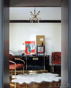 Jackie Astier's New York Apartment - hall outside the library, the brass-and-­lacquer cabinet is by Mastercraft, and the chairs are upholstered in a Pierre Frey fabric; the artworks are by James Rosenquist, left, and Astier's daughter Colette, and the walls are sprayed with automotive paint.  ELLE DECOR