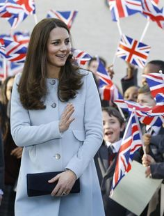 The Duchess of Cambridge wearing a stylish light blue maternity coat over her outfit while awaiting her third royal baby.