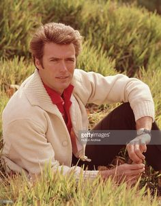 Portrait of American actor and director Clint Eastwood sitting in a field, with his leg bent and his elbow resting on his knee, 1960s. Eastwood is wearing a white cardigan over a red shirt.