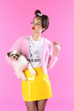 Photographer Unknown This image is has a sight pop art feel to it, this being because of the bright pink background. As well as the vibrant yellow piercing through. The overall style of the image has a certain vintage feel to it, with the model holding the dog and the way her other hand is positioned. Another element that adds to this image is the models make up, the bright red lipstick creates definition on the models face.