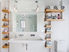 bathroom with white wall, white sink, white framed mirror, brown wooden shelves in right and left, two pendant lamps of Much Storage to Your Need and Liking in Tiny Bathroom
