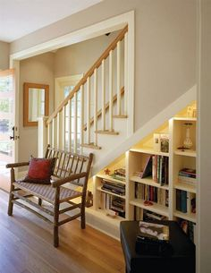 22 Brilliant Under Stairs Storage Ideas To Maximize Your Interiors In Style : Attractive Under Stair Storage Design With White Bookshelf Along With Black Ottoman Also Wooden Bench Also Red Cushion