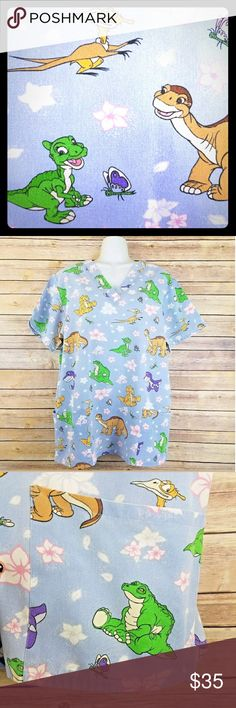 The Land Before Time Scrub Top L 90s Dinosaurs The Land Before Time patterned blue short sleeve scrub top with two front pockets. Very hard to find pattern!  Brand:  Cherokee, The Land Before Time Collection Size:  Large  Measurements (approximate):  Shoulder to Shoulder: 18.25 inches Chest: 48.5 inches Waist: 49 inches Length: 27.5 inches  Condition: Pre-loved. All over fade. Photo 7: Three small (bleach?) marks on mid back. Photo 8: Small dot on the left back shoulder. Photo 10: Tiny dot…