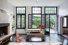 I love the dark floor and window frames along with the whitewashed brick and TON of natural light. Just so calming.