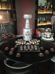 The Stanley Cup, sculpted entirely out of cake and fully edible. On the table are New York style cheesecakes dipped in Belgian Chocolate - hockey pucks :)  #nhl #stanleycup #cake #hockey