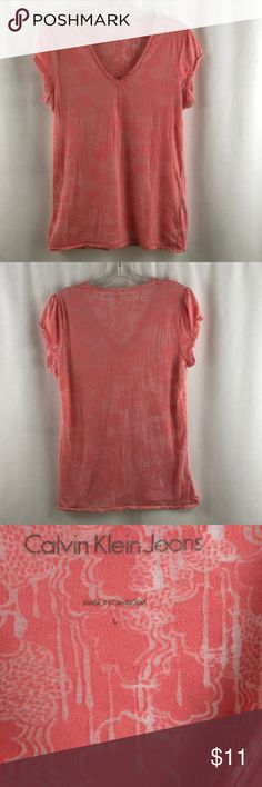 """Calvin Klein Jeans Coral t-shirt large Great semi-sheer coral t-shirt. Hard to photograph how pretty it is . Pre-owned in great condition. No holes or stains found measurements are 19.5"""" pit to pit and 25 """" back of collar to bottom of shirt Calvin Klein Jeans Tops Tees - Short Sleeve"""