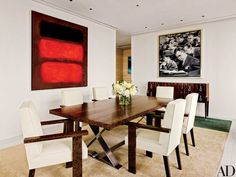 Paintings by Mark Rothko and Gerhard Richter overlook the dining room's bespoke palm-wood table and chairs, the latter upholstered in a Holland & Sherry fabric; the 1920s cabinet is by Émile-Jacques Ruhlmann, and the silk rug was custom made by Beauvais Carpets.