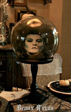 Haunted Dining Room - Some nice decorating ideas here. I like this Haunted Mansion crystal.  I think you could make it with a round globe, print out of just the face and some fake hair around it.  Nice effect in dim lighting.