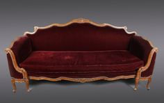 French, Late 19th/Early 20th century. Turn of the century Louis XV style sofa with carved walnut wood undulating frame with scrolling, acanthus leaf tips and flowers throughout with S scroll arms elegantly curving toward seating upholstered in dark purple to burgundy silk mohair accented with faceted nail heads.