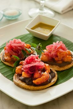 Panuchos de camarón en Agua y Sal Cebicheria. Shrimp marinated in Achiote adobo and  Guajillo pepper served over home-made fried mini corn tortillas with refried black beans, pickled red onion and Habanero pepper sauce.