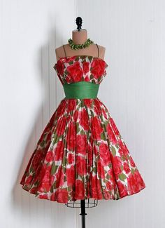 1950s sleevelss dress with bright, big red flowers and bright green sash.