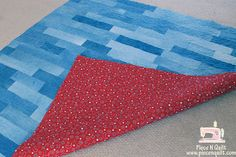 Like this denim quilt...maybe with red bandana or gingham on the back, and as a border on the front/binding?