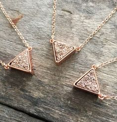 Super sparkly, rose gold druzy triangle takes center stage along a delicate…