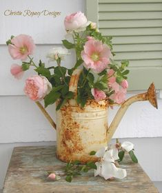 English roses and hollyhocks arranged in a rusty old watering can can bring wonderful contentment to one' soul.