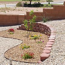 Desert Southwest landscaping on a small hillside circular driveway using retaining walls and Xeriscaping principles and methods.  (via Hometalk)