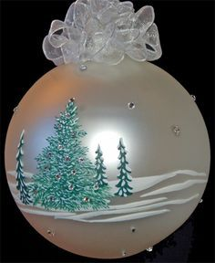 photo of glass ornament with hand painted snow covered pine trees