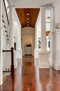 Sturdy white columns and gleaming dark floors make for a gorgeous entry and hallway.
