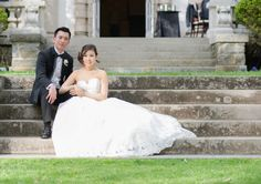 Bride and groom sitting on stairs of mansion wedding captured by Daisy Saulls Photography