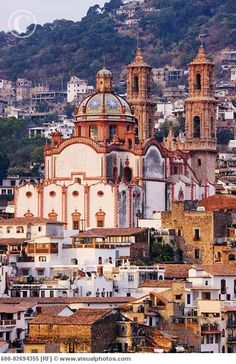 Taxco, Mexico, meandering up side of a mountain with cobblestone streets and the ornate Santa Prisca Cathedral built in the 1700s. I remember they had wild poinsettia bushes blooming when we were there around Christmas that were taller than me. They are known for the silver workmanship for sale throughout the city.