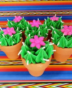 """Cinco de Mayo - More cute cacti.  These are actually store bought brownie bites.  I put them in little pots and piped green frosting on top of them.  Then I added sprinkles for """"needles"""" and a fondant flower."""