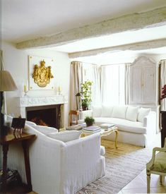 A couple of white washed or driftwood beams  Elegant country living room by Nicky Haslam