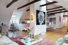 Chic attic apartment with a colorful interior and exposed beams