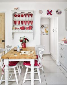 Looking for country kitchen ideas? Take a look at this white country kitchen with tiled floor, open shelving and red accents for decorating inspiration. Find more kitchen decorating and design ideas at theroomedit.com