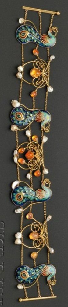 An Arts & Crafts Enamel, Fire Opal and Freshwater Pearl Dog Collar, probably England, circa 1905. Designed as four polychrome champlevé enamel peacocks with silver pallions interspersed stylised wirework blossoms bezel-set with cabochon fire opals and highlighted by pearls, counter-enamelled, joined by strands of trace link chain, gold mount, unsigned. #ArtsAndCrafts #DogCollar