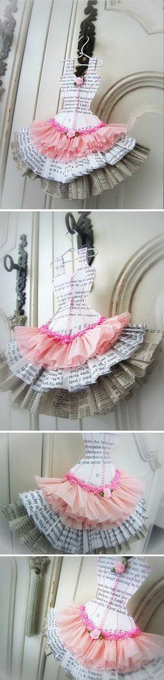 Robe faite à partir de pages de papier recyclé (romans, annuaires...) et de papier crépon. Elle est cousue avec du fil de coton rose et est soulignée d'un galon rose et de deux fleurs de satin rose. Elle mesure 19 cm de hauteur x 18 cm de largeur et est livrée avec son petit cintre blanc.                                                                                                                                                                                 Plus