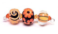petite lampwork glass round beads in two shades of coral orange over shiny black.