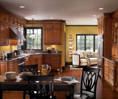"""Enjoy the depth of color, and thoughtful design of the Cherry kitchen cabinets that work hard to make this house a home. Little details, like under cabinet moulding, and the continuation of moulding and trim above the windows adds just a little something more than anticipated. It's that little bit of """"extra"""" that reflects personality and let's us call a design our own."""