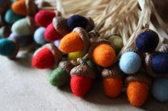 Get wool for felting (craft store) roll the wool into small balls, wet with hot water and add a little bit of soap. continue rolling the ball in your hands for about ten minutes, occasionally adding soap, until it is firm. mold into the shape of an acorn and glue into the cap using fabric glue or even krazy glue or guerilla glue. for  the holidays add a little glitter for some extra sparkle :)