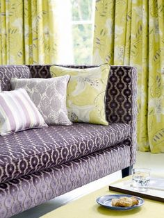 Bloomsbury   Sanderson. Sofa with colorful print pillows.  WHAT PATTERN IS THE CURTAINS?
