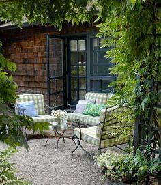 Black door trim and trellises, black wrought iron furniture with green/white checks.