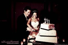 A bride and groom cut their wedding cake, with three square tiers, decorated with black ribbon and a few flowers. The cake is topped with a silver M monogram. The bride's embellished sweetheart ballgown, and crystal chandelier earrings and tiara sparkle in the light of the candles around the cake. The couple held their wedding and reception in the premier Peabody Hotel, Orlando, and engaged The John Parker Band to entertain the crowd, the final perfect touch…