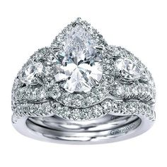 14K White Gold Pear Shaped 3-Stone Halo Diamond Engagement Ring. This ring features 1.20cttw of round pave set diamonds with two large pear shaped side diamonds