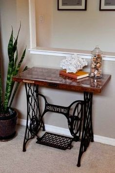 Glass-topped printer's draw set on sewing machine treadle. Awesome! Great way to display items without having to dust them all the time. Via FleaChic