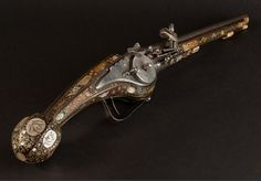 An Extremely Rare Petronel from the 16th / 17th century (1600) A long wheel lock petronel or holster pistol in the Dresden style. The Pistol with a fruitwood stock inlaid with mother of pearl and horn plaques of grotesques and animals ending in a fluted pear-shaped pommel with an iron trigger-guard and the ramrod-pipes and fore-end cap each of engraved horn (ramrod and some mother of pearl and ivory replaced). Most likely German.