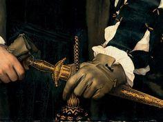 Dettagli 3. Hans Holbein il Giovane: Ritratto di Charles de Solier, signoredi Morette. Olio su tavola di quercia, del 1534-35. Gemaldegalerie Alte Meister, Dresda. La mano guantata si appoggia al pugnale istoriato e legato alla cintura con una bella nappa. E' uno dei ritratti più belli di questo grande pittore: un uomo bello, maturo, forte, che Holbein ha ritratto in modo magnifico.